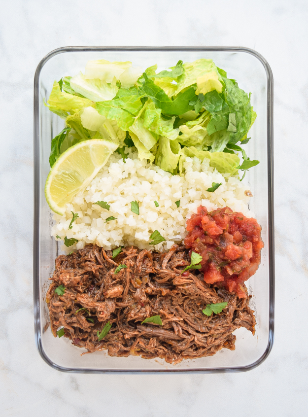 meal prep chipotle beef bowls in glass container with cauliflower rice, lettuce, and salsa