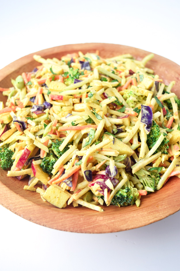 close up view of whole30 curried broccoli slaw in wooden bowl
