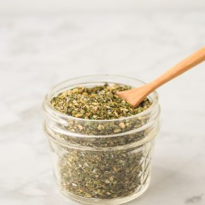 greek seasoning blend in mason jar with bamboo spoon