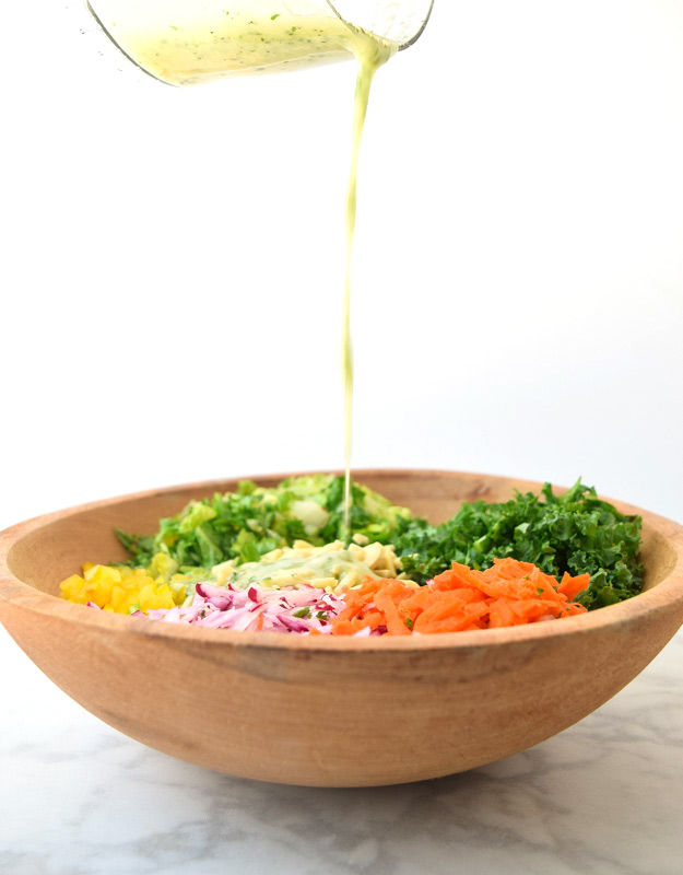 garlic lemon vinaigrette pouring over chopped detox salad
