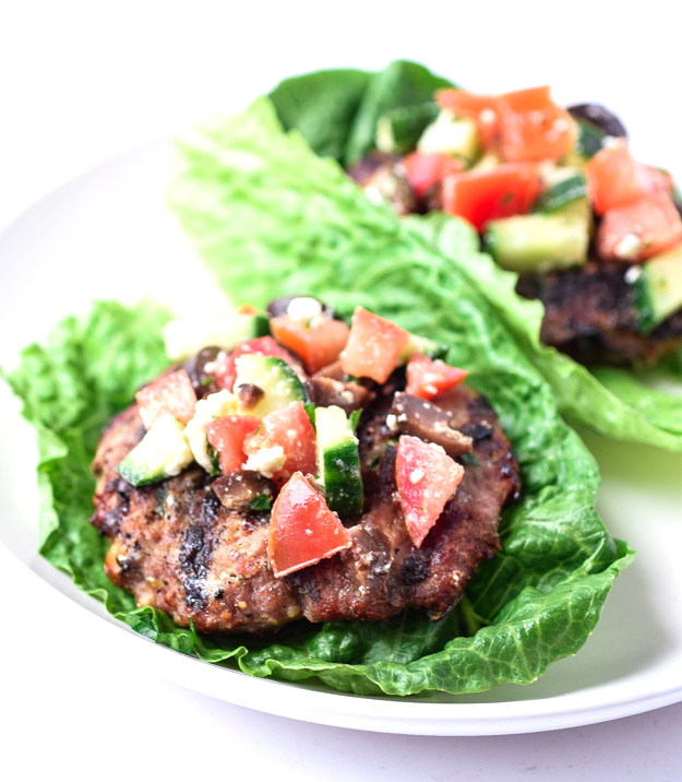 plated greek turkey burgers on lettuce leaves with greek topping